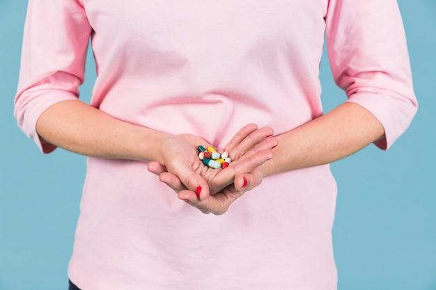 Section médiane d'une femme tenant une variété de capsules dans la main Photo gratuit