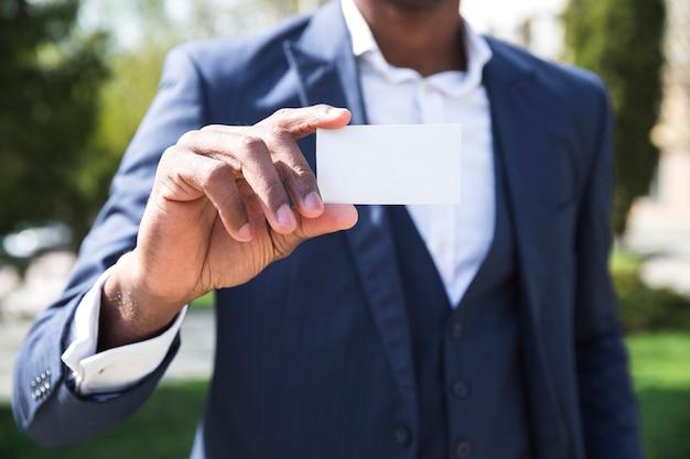Section médiane d'un homme d'affaires montrant une carte de visite blanche Photo gratuit