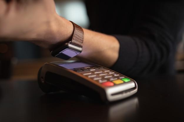 Section Médiane De L'homme Faisant Payer Via Smartwatch Photo gratuit