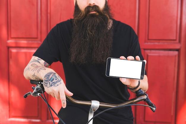 Section médiane d'un homme tatoué sur sa main tenant un téléphone portable à la main Photo gratuit