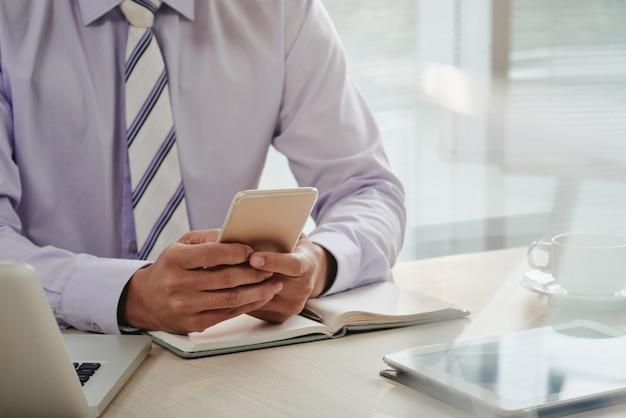 Section médiane d'un homme vérifiant ses e-mails sur smartphone Photo gratuit
