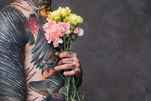 Section médiane d'un jeune homme tatoué torse nu tenant un œillet dans les mains Photo gratuit