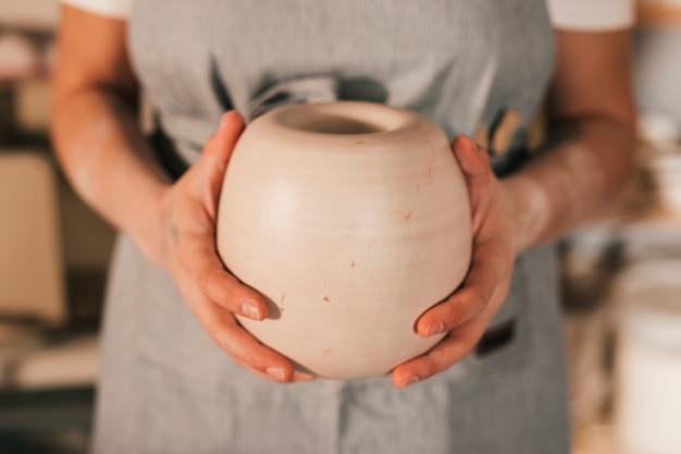 Section médiane de la main d'une potière féminine tenant un pot à la main Photo gratuit