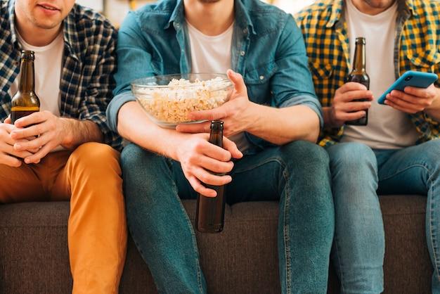 Section médiane de trois hommes assis ensemble sur un canapé tenant des bouteilles de bière à la main Photo gratuit