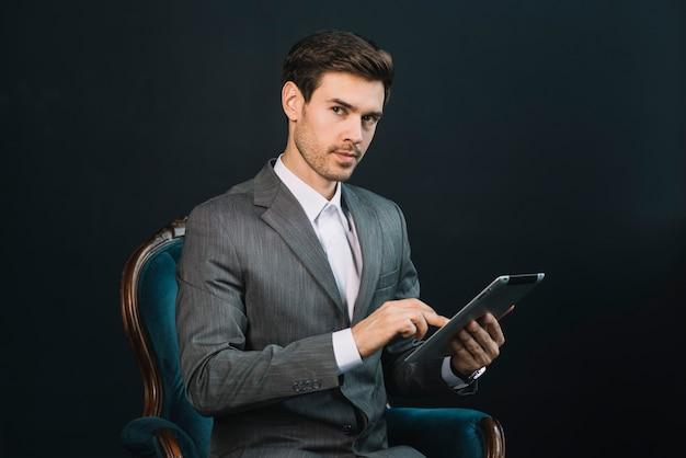 Un séduisant jeune homme d'affaires assis dans un fauteuil à l'aide d'une tablette numérique Photo gratuit