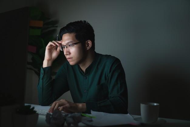 Séduisant jeune homme asiatique assis sur une table de bureau regardant un ordinateur portable Photo Premium