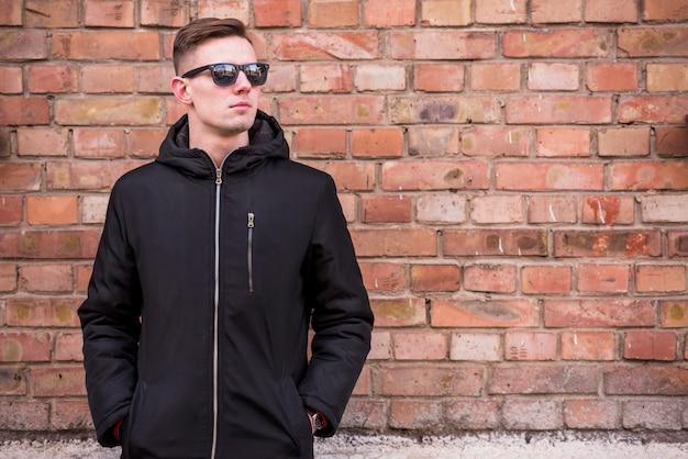 Un séduisant jeune homme avec les mains dans la poche devant un mur de briques Photo gratuit