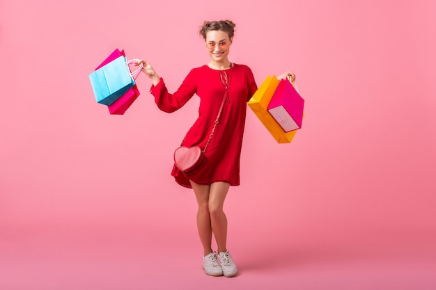 Séduisante Heureuse Souriante Femme élégante Accro Du Shopping En Robe Rouge à La Mode Tenant Des Sacs Colorés Sur Un Mur Rose Isolé, Vente Excité, Tendance De La Mode Printemps été Photo gratuit