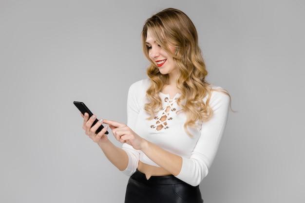 Séduisante jeune femme d'affaires blonde en vêtements noir et blancs souriant tenant un téléphone mobile Photo Premium
