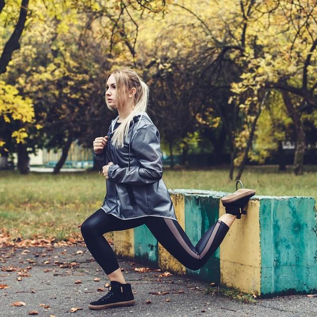 Séduisante jeune fille faire des exercices sportifs dans un parc de la ville à temps pluvieux. Photo Premium