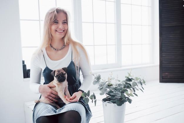Séduisante Jeune Fille Avec Mignon Chien Carlin Sur Les Mains Photo Premium