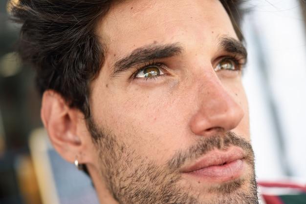 Séduisante jeune homme aux cheveux noirs et coiffure moderne, porter des vêtements décontractés à l'extérieur Photo Premium