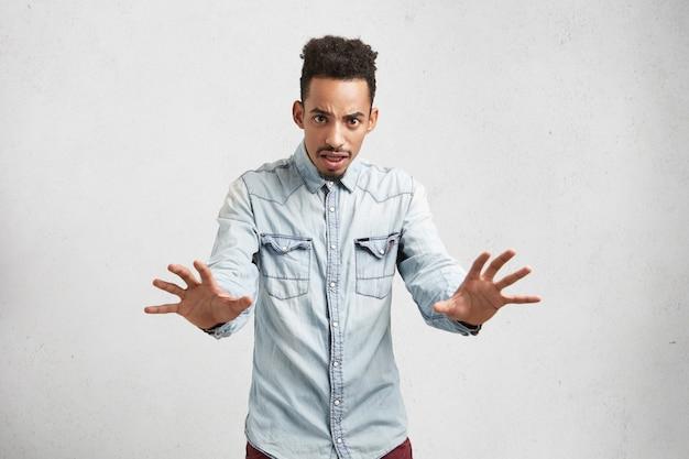 Séduisante Jeune Homme Fait Un Geste Effrayé Avec Les Paumes, Se Défend Photo gratuit