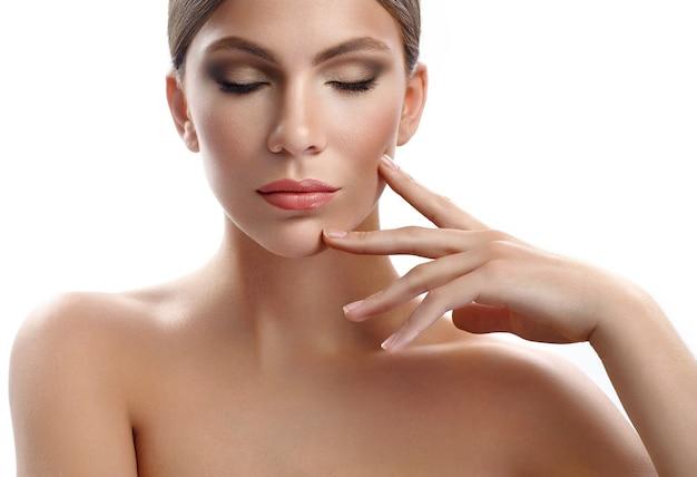 Séduisante jeune mannequin touchant son visage sensuellement Photo Premium