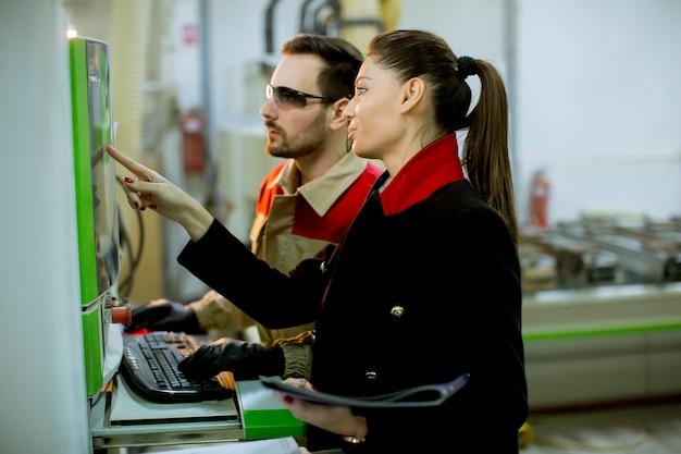 Séduisante jeune technicienne effectuant une inspection dans le département de production de l'usine Photo Premium