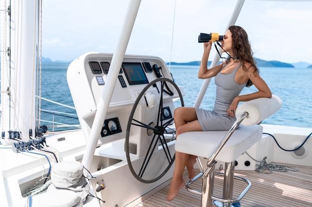 Séduisante et magnifique brune assise et conduisant sur un yacht moderne et tenant des jumelles Photo Premium