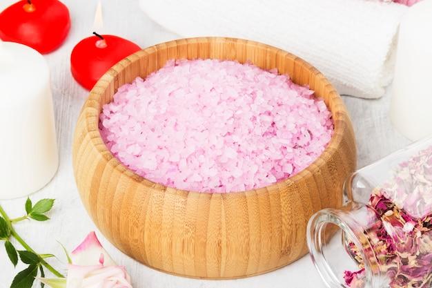 Sel De Bain Avec L'arôme D'une Rose Dans Un Bol En Bois, Des Pétales Et Une Rose Rose Fraîche, Des Serviettes Et Des Bougies Sur Fond Blanc Photo Premium