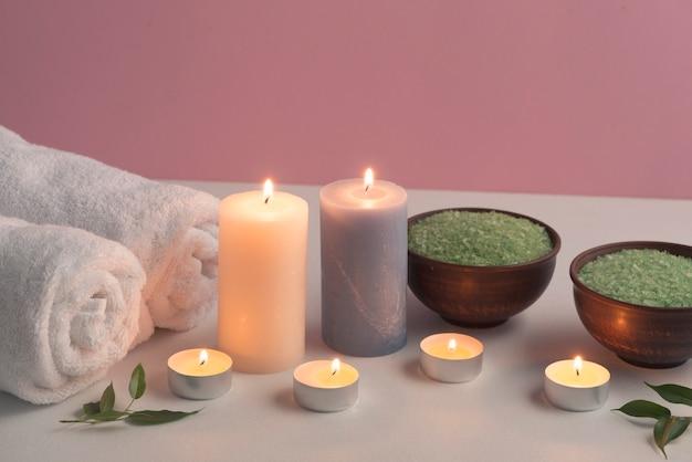 Sel de bain à base de plantes vertes et serviettes avec des bougies allumées sur table blanche Photo gratuit