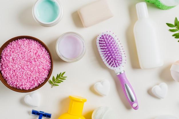 Sel rose; brosse à dents et produits cosmétiques sur fond blanc Photo gratuit