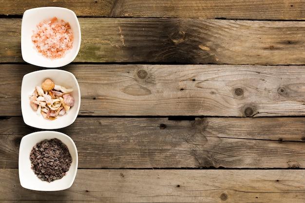 Sel rose et noir avec des coquillages dans un bol sur la table en bois Photo gratuit