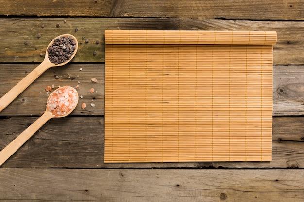 Sel rose et noir dans des cuillères en bois avec tapis sur fond en bois Photo gratuit