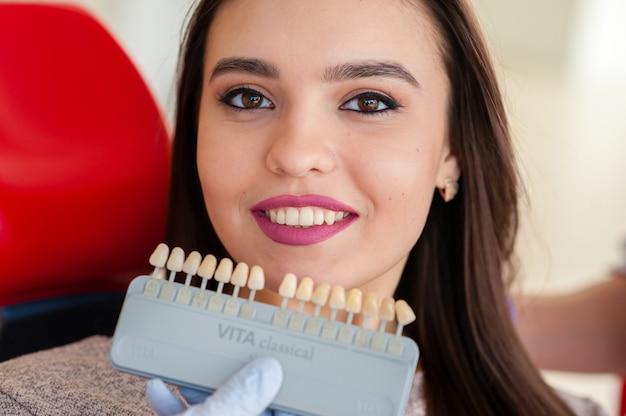 Sélection de la couleur des dents pour une belle fille en dentisterie. Photo Premium