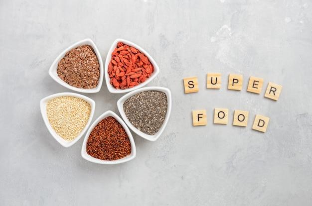 Sélection de super-aliments dans des bols blancs sur fond de béton gris. Photo Premium