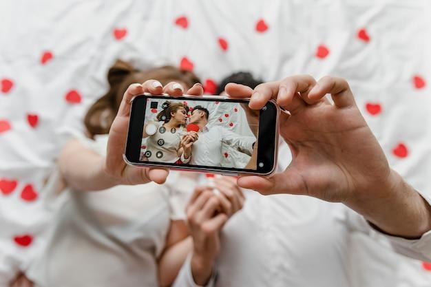 Selfie Sur L'écran Du Téléphone De L'homme Et De La Femme Amoureuse Au Lit Photo Premium