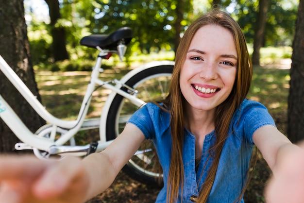 Selfie d'une femme souriante à côté du vélo Photo gratuit