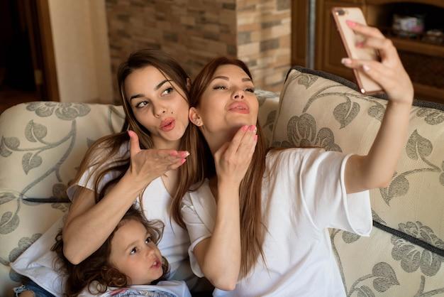Selfie portrait de deux jeunes filles et petite fille sur le canapé à la maison. Photo Premium