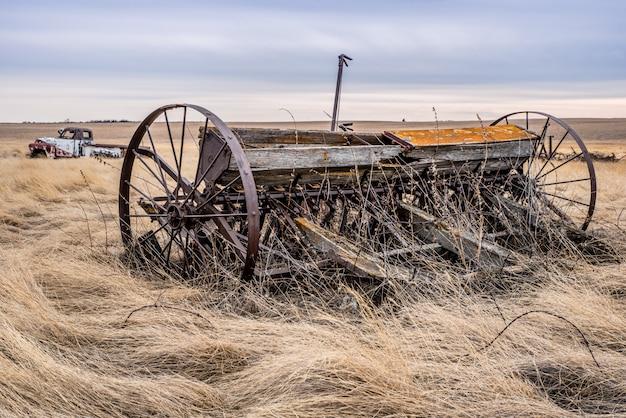 Un Semoir Pionnier Vintage Avec Un Camion Classique En Arrière-plan En Saskatchewan, Canada Photo Premium