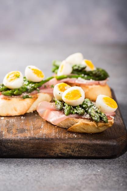 Sendwich frais avec du jambon, des asperges et des œufs de caille Photo Premium
