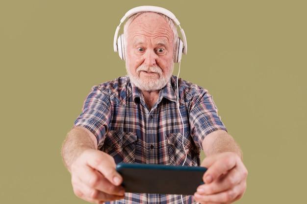Senior angle jouant de la musique Photo gratuit