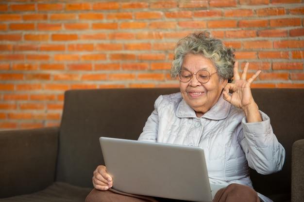 Senior Asian Woman Asseyez-vous Sur Le Canapé, Passez Du Temps Libre à La Maison En Utilisant Les Réseaux Sociaux En Vous Amusant à Discuter Avec Des Amis Ou Des Enfants, Profitez D'une Nouvelle Application, Concept D'utilisateur Avancé Avancé. Photo Premium