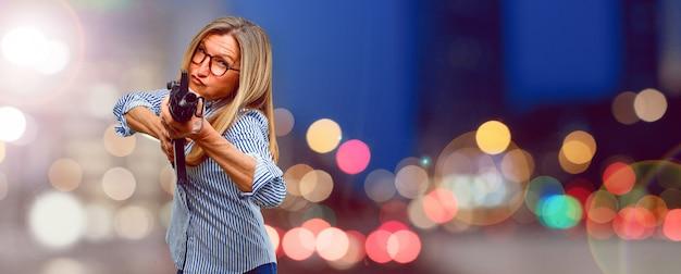 Senior belle femme avec un fusil. concept de conflit Photo Premium