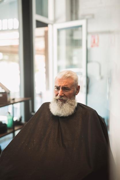 Senior client mâle avec cape dans le salon de coiffure Photo gratuit