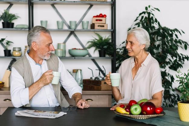 Senior couple assis dans la cuisine prenant son petit déjeuner ensemble Photo gratuit