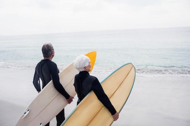 Senior couple en combinaison de surf tenant la planche de surf sur la plage Photo Premium