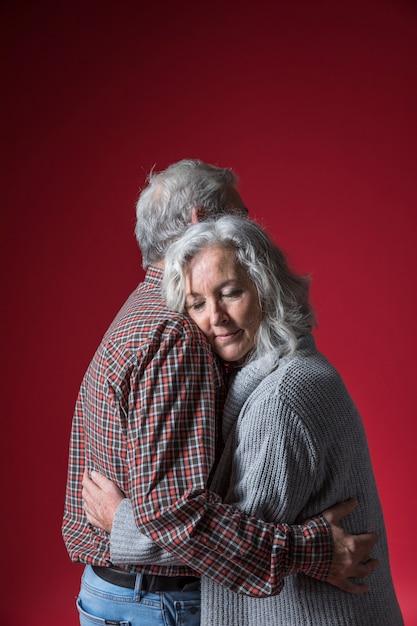 Senior couple embrassant debout sur fond rouge Photo gratuit