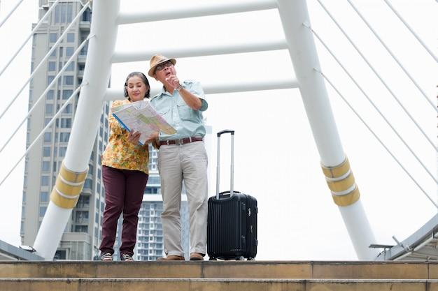 Senior couple est debout tenant la carte pour rechercher des destinations dans les rues. Photo Premium