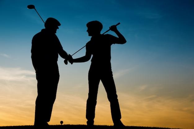 Senior couple jouant au golf au coucher du soleil Photo Premium