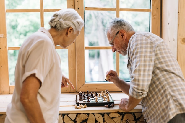 Senior couple jouant aux échecs sur le rebord de la fenêtre Photo gratuit
