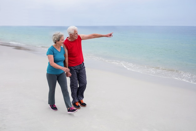 Senior couple parlant et marchant sur la plage Photo Premium