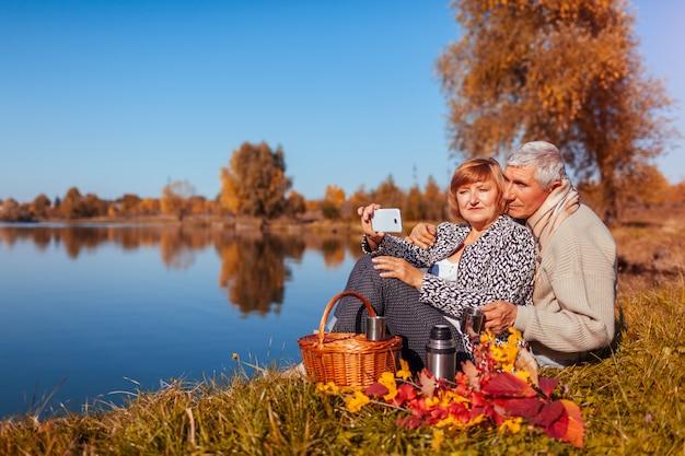Senior couple prenant selfie tout en pique-nique au bord du lac en automne Photo Premium