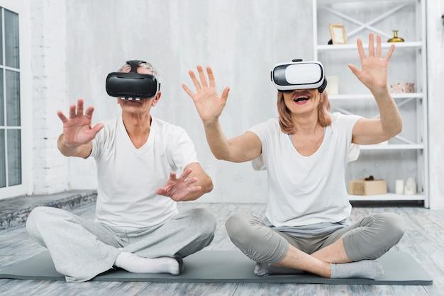Senior couple senior assis sur un tapis gris s'amuser avec des lunettes de réalité virtuelle Photo gratuit