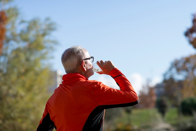 Senior coureur de l'eau potable après un jogging Photo Premium