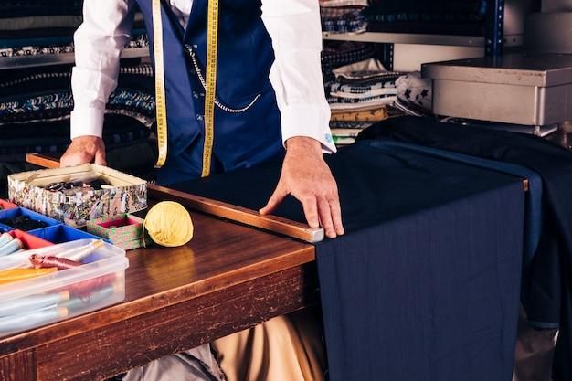 Senior créateur de mode prenant la mesure du tissu sur la table en bois Photo gratuit