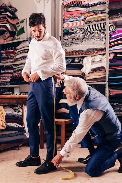 Senior créateur de mode prenant la mesure de la jambe du client dans la boutique Photo gratuit