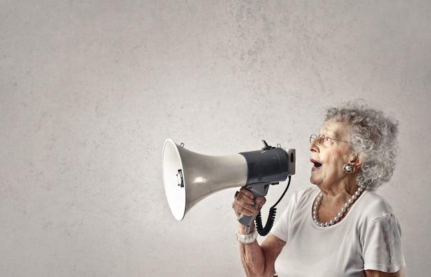 Senior dame parlant dans un mégaphone Photo Premium