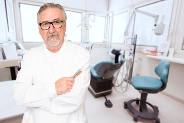 Senior dentiste debout dans son bureau Photo Premium